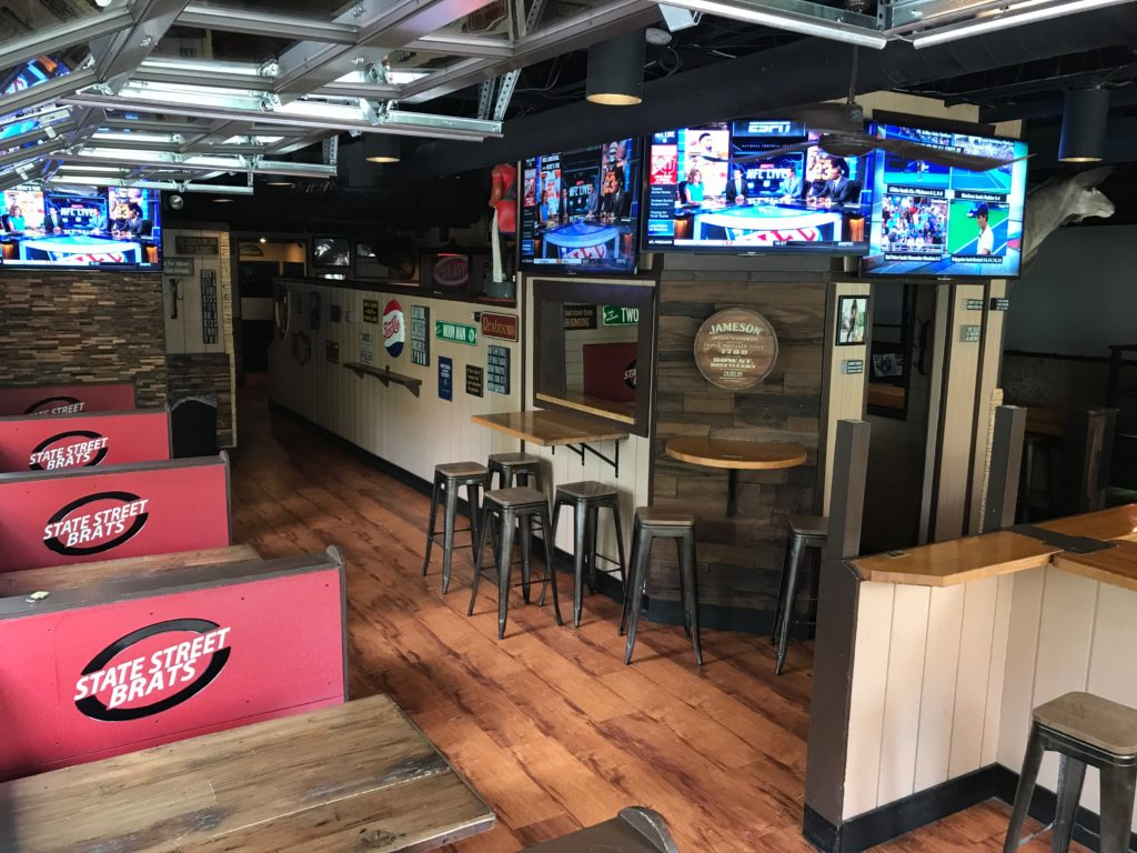 Photo of interior private party space - contains bar stools, TVs, and benches